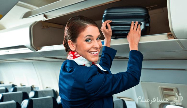 مهماندار هواپیما در حال بالا گذاشتن چمدان